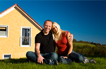 Couple sitting in the grass outside a home